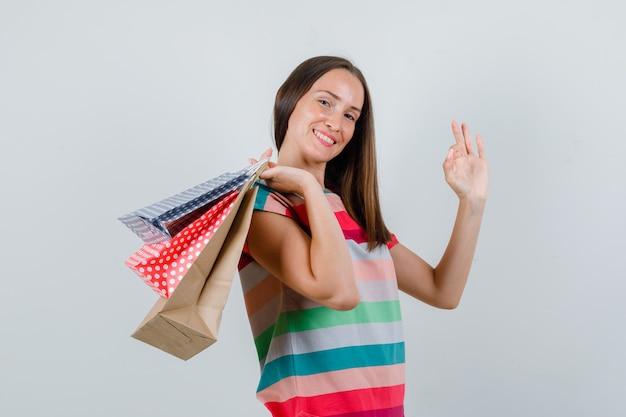 Молодая женщина в футболке держит бумажные пакеты с знаком ок и выглядит счастливым, вид спереди.