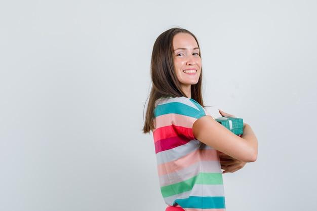 Молодая женщина в футболке обнимает настоящие коробки и выглядит веселой.