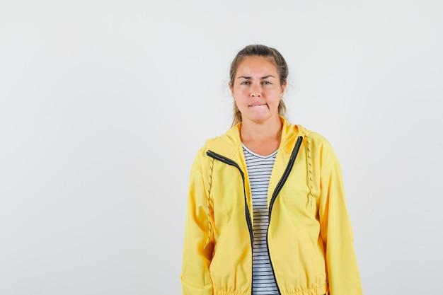 Tシャツを着た若い女性、彼女の唇を噛み、賢明に見えるジャケット、正面図。 無料写真
