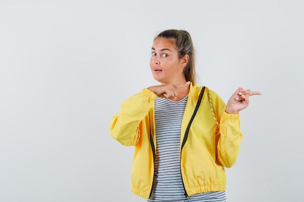 Tシャツを着た若い女性、脇を向いて自信を持って見えるジャケット、正面図。