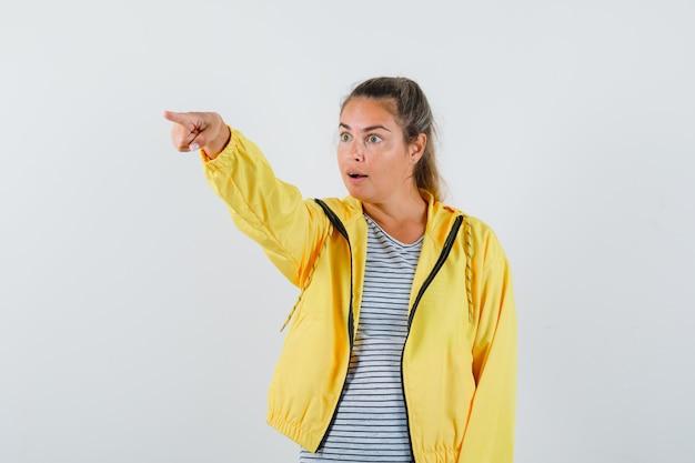 Молодая женщина в футболке, пиджак, указывая в сторону и глядя изумленно, вид спереди.