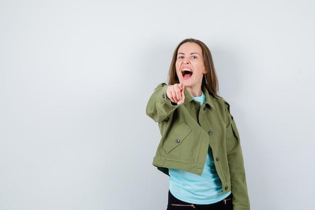 티셔츠를 입은 젊은 여성, 앞을 가리키고 정력적으로 보이는 재킷.