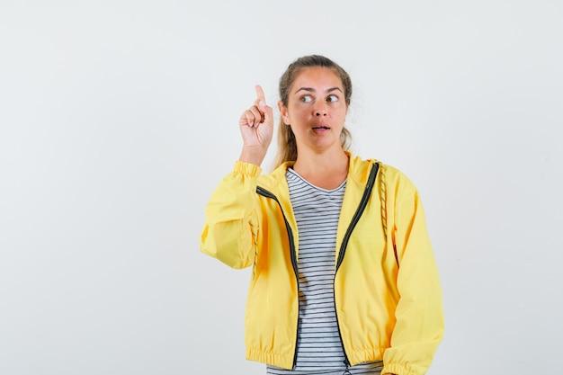 Tシャツを着た若い女性、上向きで物思いにふけるジャケット、正面図。