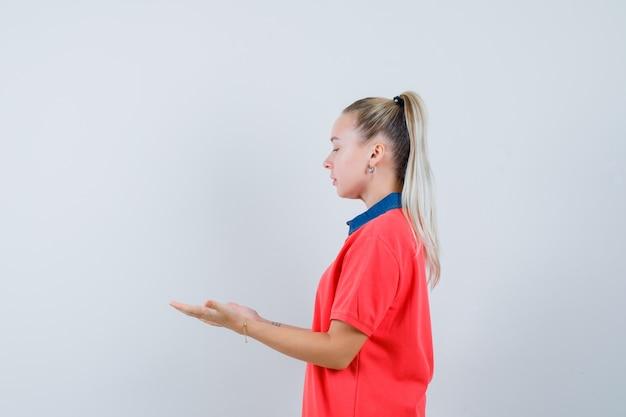 Молодая женщина в футболке смотрит на свои вытянутые руки и выглядит сосредоточенной