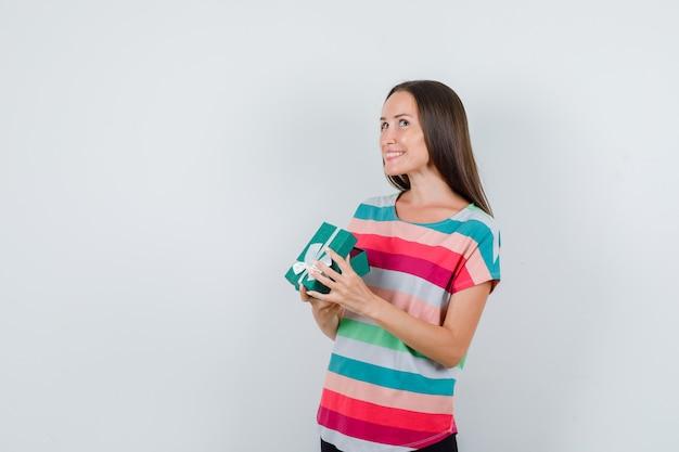 Tシャツを着た若い女性、開いたギフトボックスを保持し、興奮して見えるパンツ、正面図。