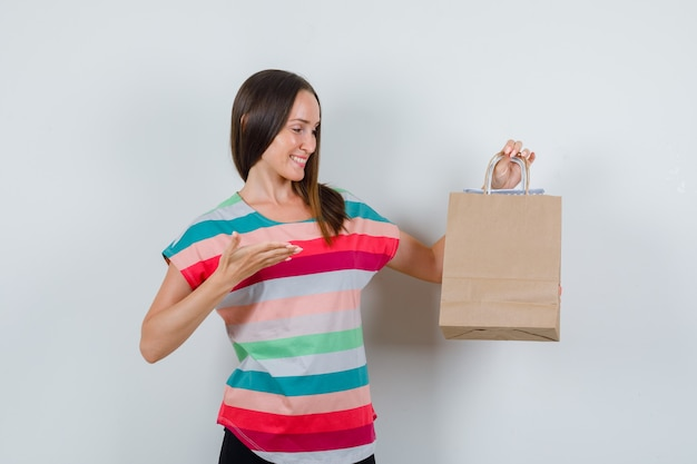 Tシャツを着た若い女性、紙袋を見せて幸せそうに見えるズボン、正面図。