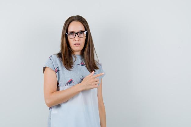 横向きでがっかりしているtシャツの若い女性、正面図。