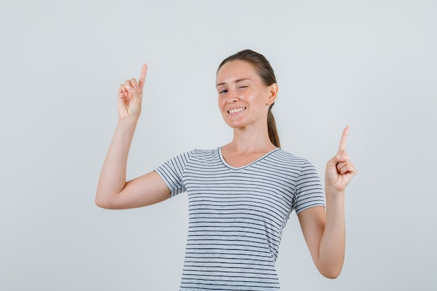 Tシャツを着た若い女性が上を向いてウインクして元気に見える、正面図。