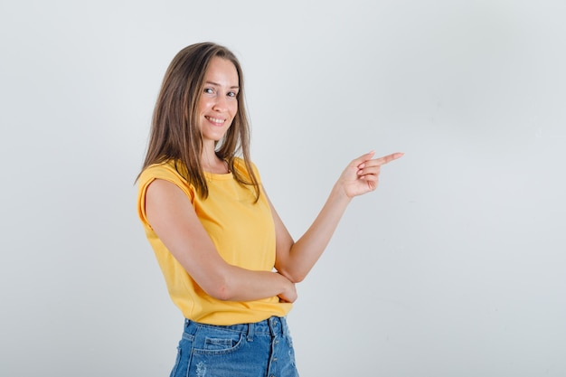 Tシャツを着た若い女性、指を横に向けて元気に見えるショートパンツ