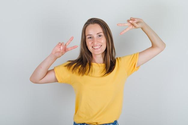 Молодая женщина в футболке, шортах показывает жест мира и выглядит весело