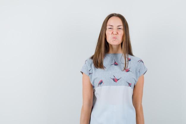 面白い表情を見せて欲求不満に見えるtシャツの若い女性、正面図。