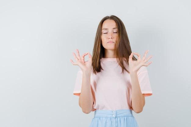 Tシャツを着た若い女性、目を閉じてokサインをしているスカート、落ち着いて見える、正面図。