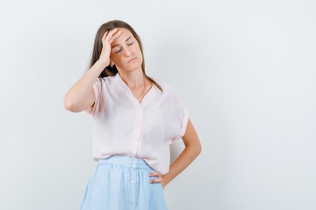 Tシャツを着た若い女性、頭痛があり、疲れているように見えるスカート、正面図。