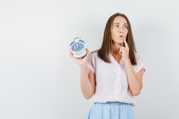 Молодая женщина в футболке, юбке держит будильник и смотрит задумчиво, вид спереди.