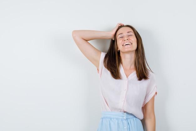 T- 셔츠, 치마 머리에 손을 잡고 귀여운, 전면보기를 찾고있는 젊은 여자.
