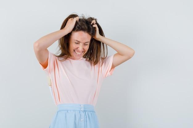 Tシャツを着た若い女性、髪に手をかざしてラッキーに見えるスカート、正面図。