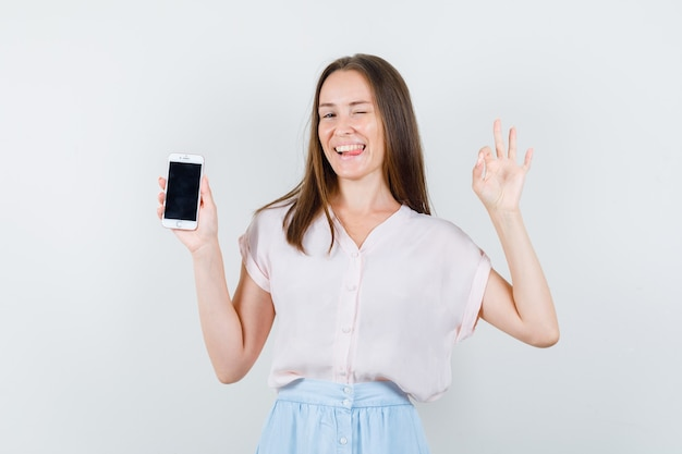 Tシャツを着た若い女性、okのサインと面白い携帯電話を保持しているスカート、正面図。