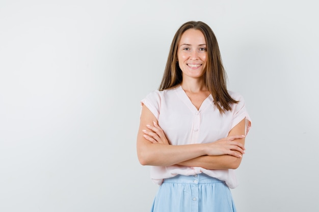 Молодая женщина в футболке, юбка стоит со скрещенными руками и выглядит позитивно, вид спереди.