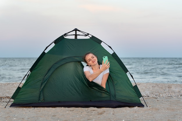 テントの中で若い女性が自分撮りをします。海岸でのキャンプ。