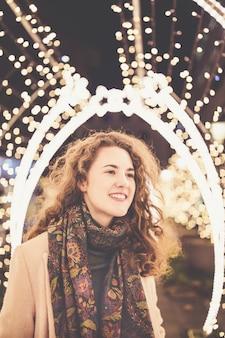 Молодая женщина в переулке с украшением рождественских огней