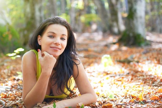 黄色の葉の上に横たわる秋の森の若い女性、背景に輝く太陽