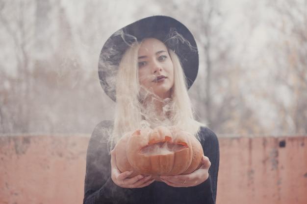 秋の森の中で白い煙が入ってハロウィーンのカボチャを保持している黒い服を着た若い女性
