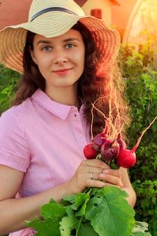 Молодая женщина в саду в шляпе и держит кучу свежего редиса в солнечный вечер
