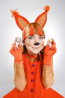 Молодая женщина в образе красной белки с грецкими орехами