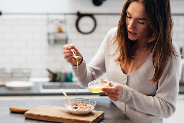 부엌에 있는 젊은 여성이 그래놀라에 꿀을 추가합니다.