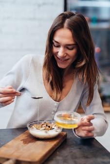 부엌에 있는 젊은 여성이 뮤즐리에 꿀을 추가합니다.