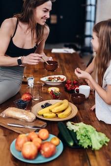 小さな女の子のために皿に食べ物を置く台所の若い女性。