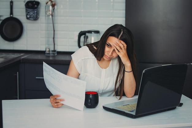ノートパソコンで作業キッチンで若い女性