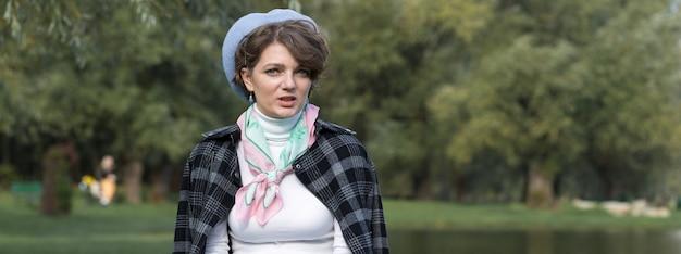 公園の若い女性が携帯電話で話します。フランス風のかわいい女の子の肖像画。