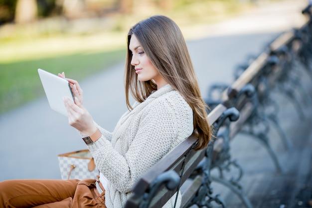 Молодая женщина в парке с планшетом