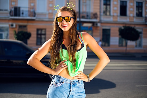 그녀의 머리에 녹색 티셔츠, 청바지, sunglases 및 네온 별을 입고 거리에서 젊은 여자