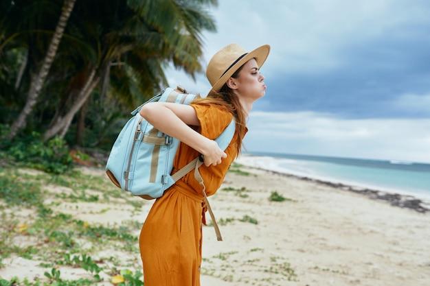 ヤシの木と熱帯のビーチで若い女性