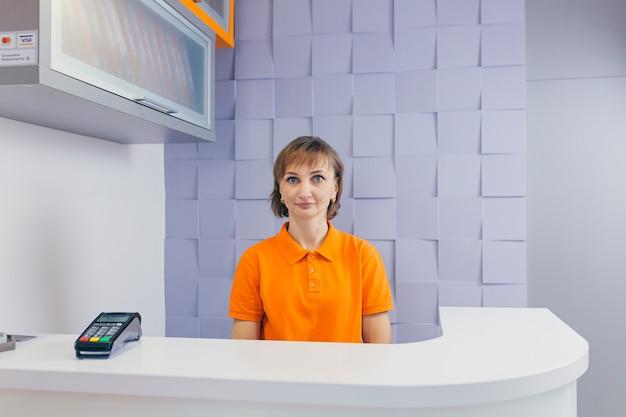 Молодая женщина в зале ожидания интервью, сидя на диване в коридоре кабинета стоматолога