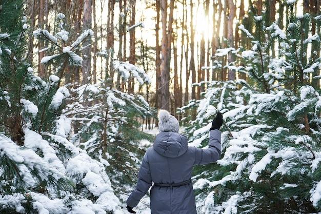日没の冬の森の若い女性。閉じる。