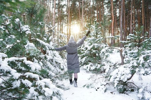 日没の冬の森の若い女性。