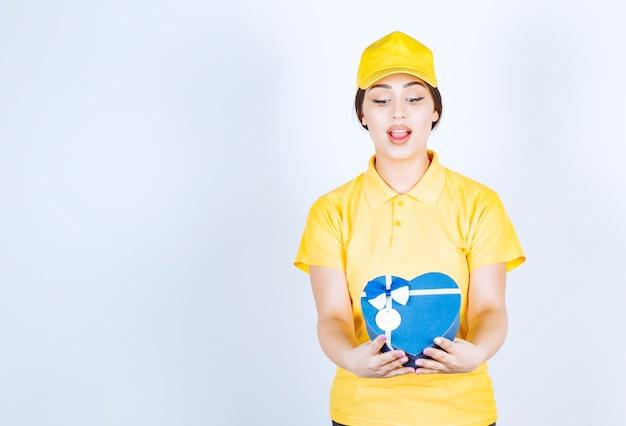 ハート型の箱を持ってそれを見ている黄色いユニシェイプの若い女性