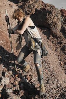 ハイスティックの助けを借りて岩に登る破れた服を着た若い女性