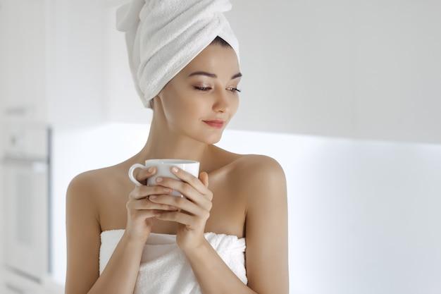 Молодая женщина в полотенце, наслаждаясь кофе в домашних условиях.