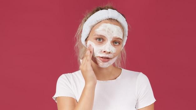 綿のパッドで彼女の顔から化粧を取り除くタオルの若い女性。肌をきれいにするためにスポンジとローションを使用している女の子