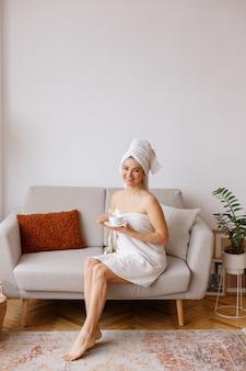 リビングルームでカップとタオルで若い女性