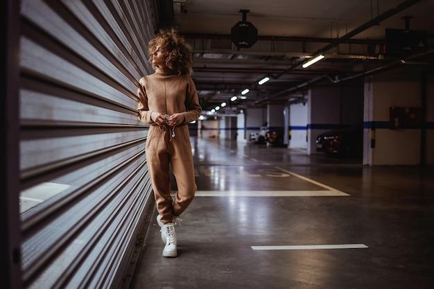 ガレージのドアに立って、それを通して見ているトラックスーツの若い女性