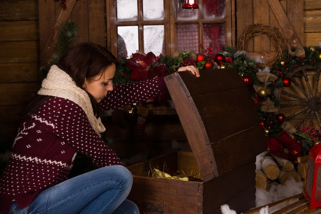 トレンディな冬のファッションの若い女性がクリスマスの装飾品で家の中にヴィンテージの木製トランクを開きます。