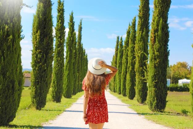 ヒノキの木、イタリアのトスカーナの風景の中の若い女性