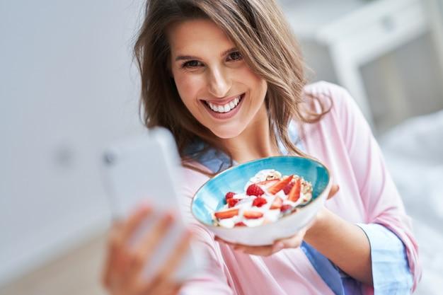 Молодая женщина в нижнем белье ест хлопья