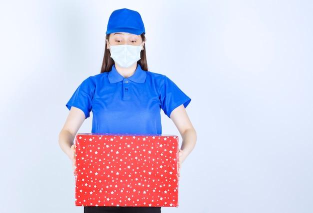 クリスマスプレゼントを保持している制服と医療マスクの若い女性。