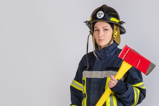 斧を持つ消防士の制服を着た若い女性